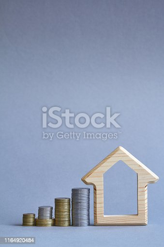 istock A wooden figurine of house with several columns of coins nearby on gray background, the concept of buying or renting a building, selective focus 1164920484