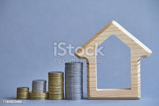 istock A wooden figurine of house with several columns of coins nearby on gray background, the concept of buying or renting a building, selective focus 1164920485
