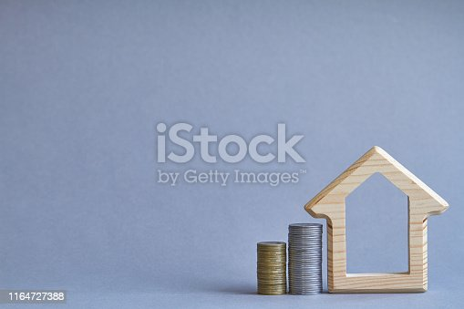 istock A wooden figurine of house with two columns of coins nearby on gray background, the concept of buying or renting a building, selective focus 1164727388