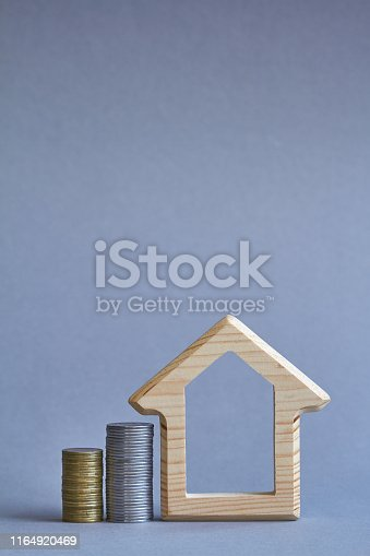 istock A wooden figurine of house with two columns of coins nearby on gray background, the concept of buying or renting a building, selective focus 1164920469