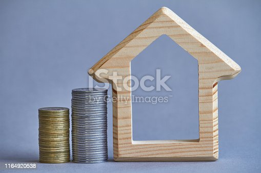 istock A wooden figurine of house with two columns of coins nearby on gray background, the concept of buying or renting a building, selective focus 1164920538
