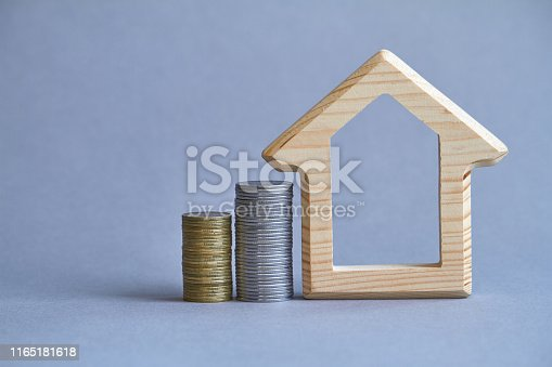 istock A wooden figurine of house with two columns of coins nearby on gray background, the concept of buying or renting a building, selective focus 1165181618