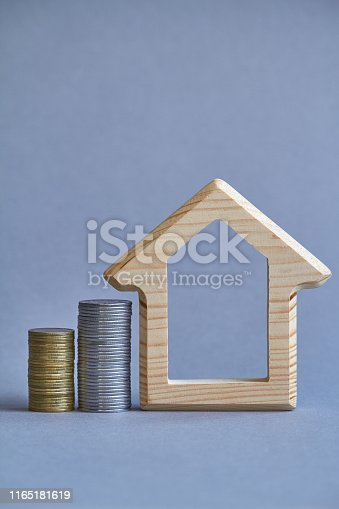 istock A wooden figurine of house with two columns of coins nearby on gray background, the concept of buying or renting a building, selective focus 1165181619