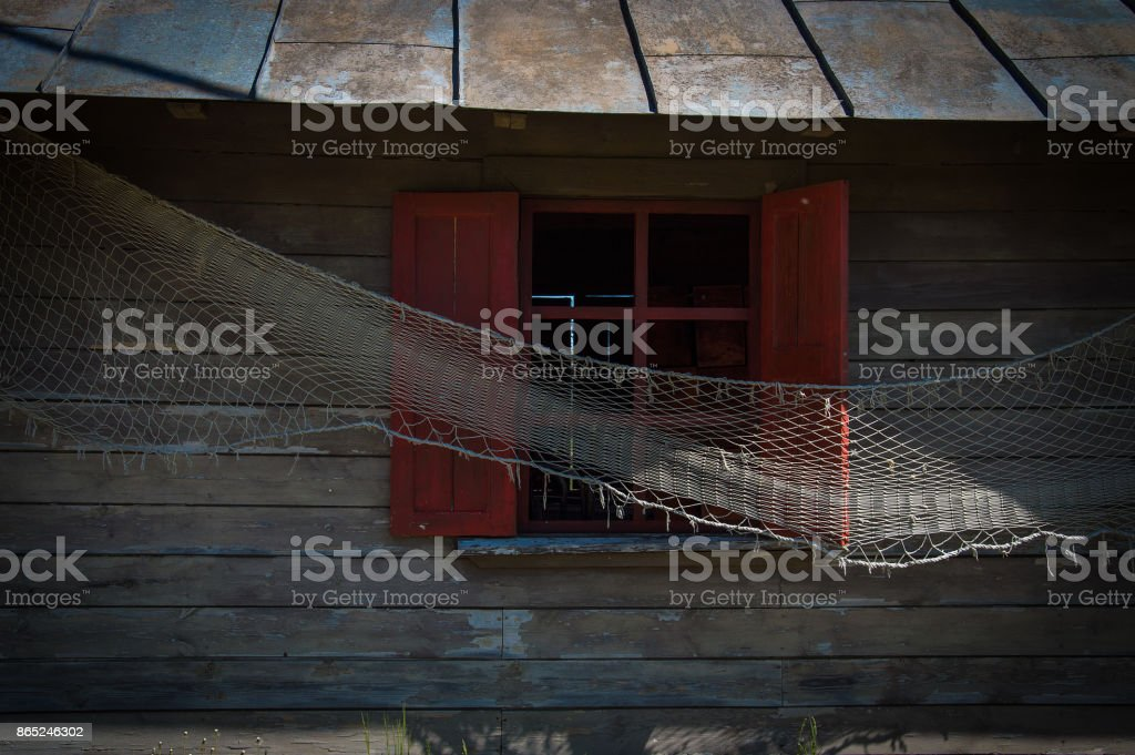 Wooden fisherman house with a window with red blinds and window frames, tinplate roof and fishing net put out for drying stock photo