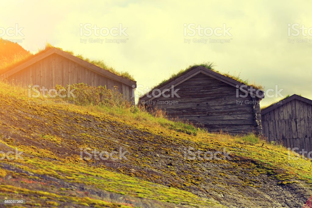 Wooden fishermen's houses with green grass on roofs against cloudy sky on mountain foto de stock royalty-free