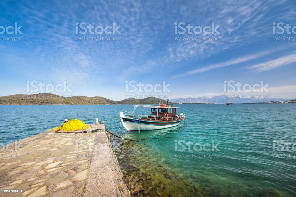 Wooden fishing boat and yachts anchored at the tropical waters of the famous gulf of Elounda, the village of celebrities, near Spinalonga, Crete, Greece. stock photo