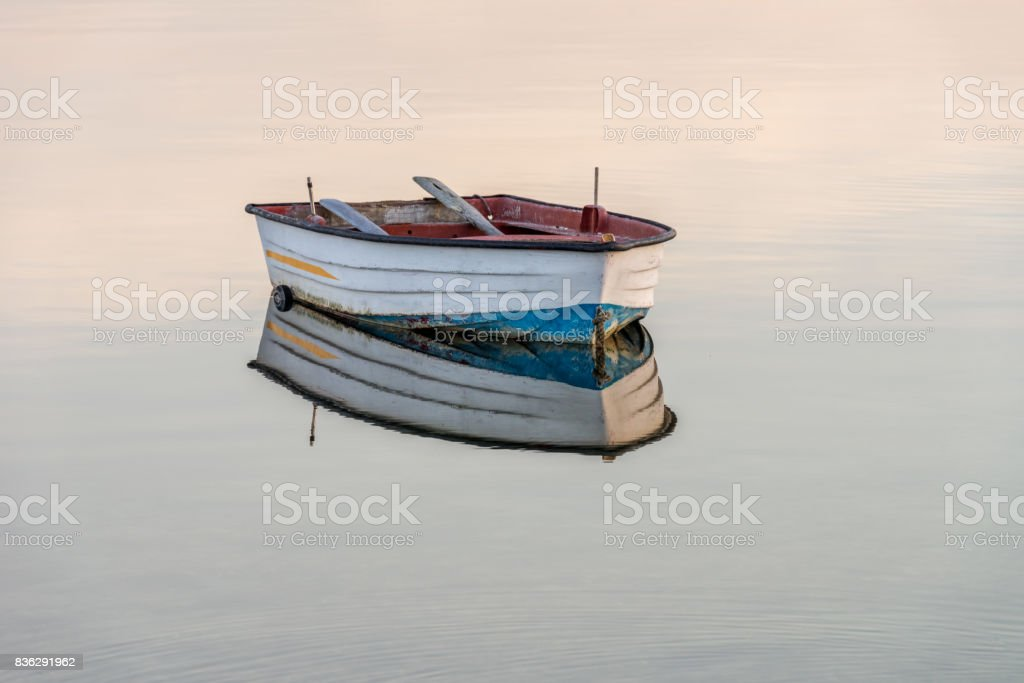 wooden fishing boat on a background of water stock photo