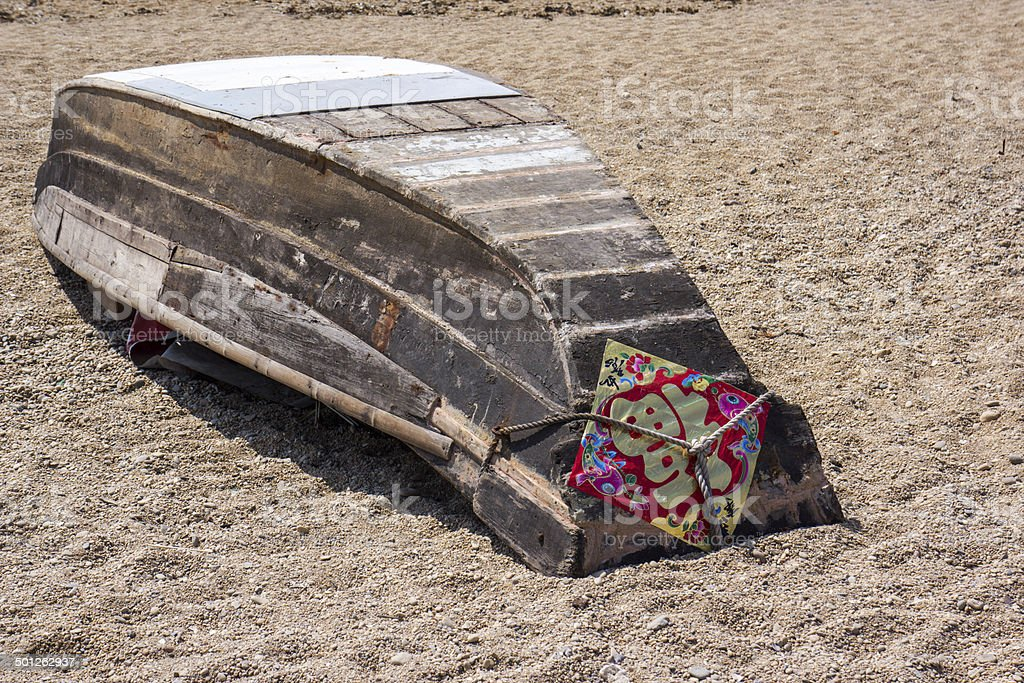 wooden fishing boat upside down on sands, with a Chinese word \'Fu\' on...