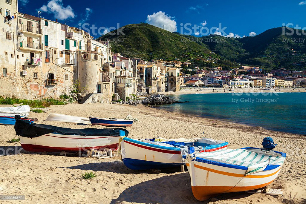 wooden fishing boats on the old beach of Cefalu stock photo
