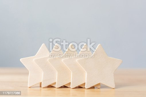 1133580311 istock photo Wooden five star shape on table. The best excellent business services rating customer experience concept 1179727086