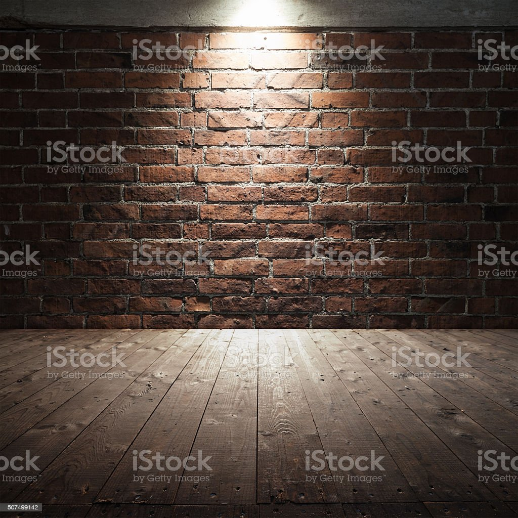 Wooden floor and red brick wall with spot light stock photo