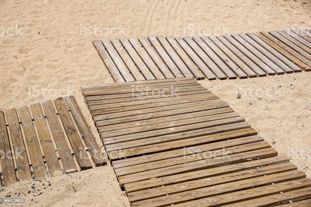 Wooden floor on golden sandy beach - foto stock