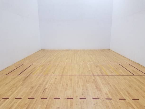 wooden floor on racketball court with white wall stock photo