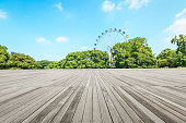 wooden floor square and playground ferris wheel in the city park,beautiful landscape