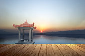 Wooden floor with a Chinese gazebo building on the lake with a dramatic sky background