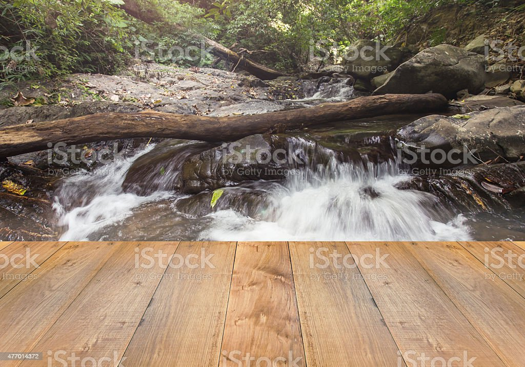 wooden floor with Beautiful waterfall in deep forest stock photo
