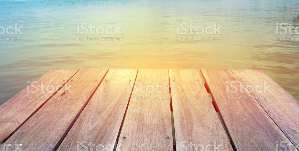 Wooden floor with deep blue sea on background in vintage color theme stock photo