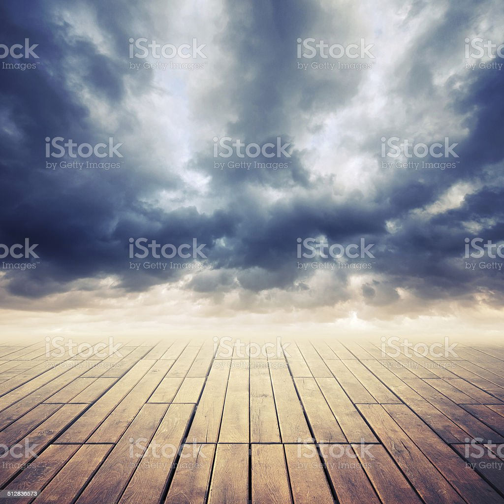 Wooden floor with perspective and stormy cloudy sky, toned effec stock photo