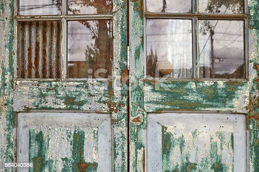 Closeup view of old wooden folding doors in vintage style with painting color peeled off