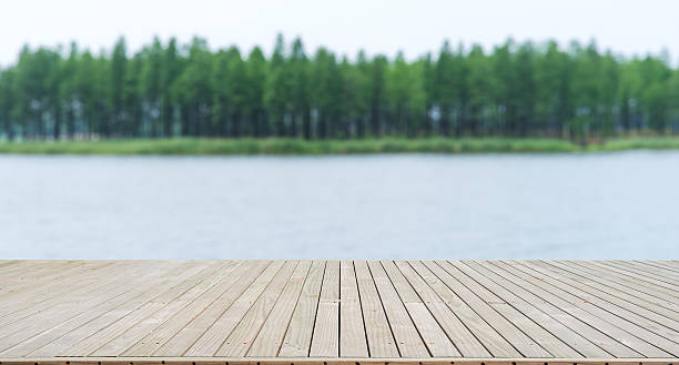 wooden footbridge beside river - pier stock photos and pictures
