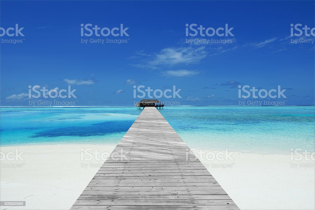 Wooden footbridge leading to overwater villa stock photo