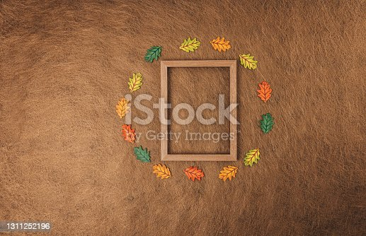 Wooden frame and bunch of autumn leaves on brown background. Flat lay concept.