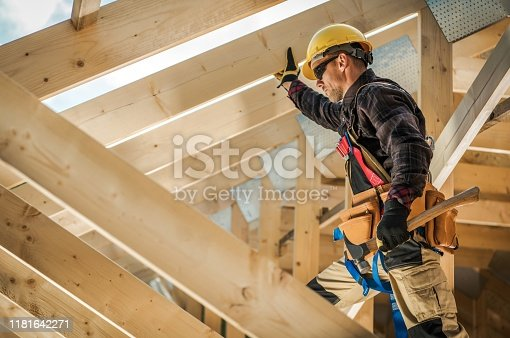 Construction Worker on Duty. Caucasian Contractor and the Wooden House Frame. Industrial Theme.
