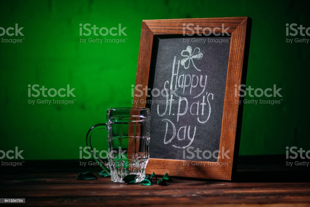 wooden frame with happy st patricks day inscription and empty beer glass on table – zdjęcie