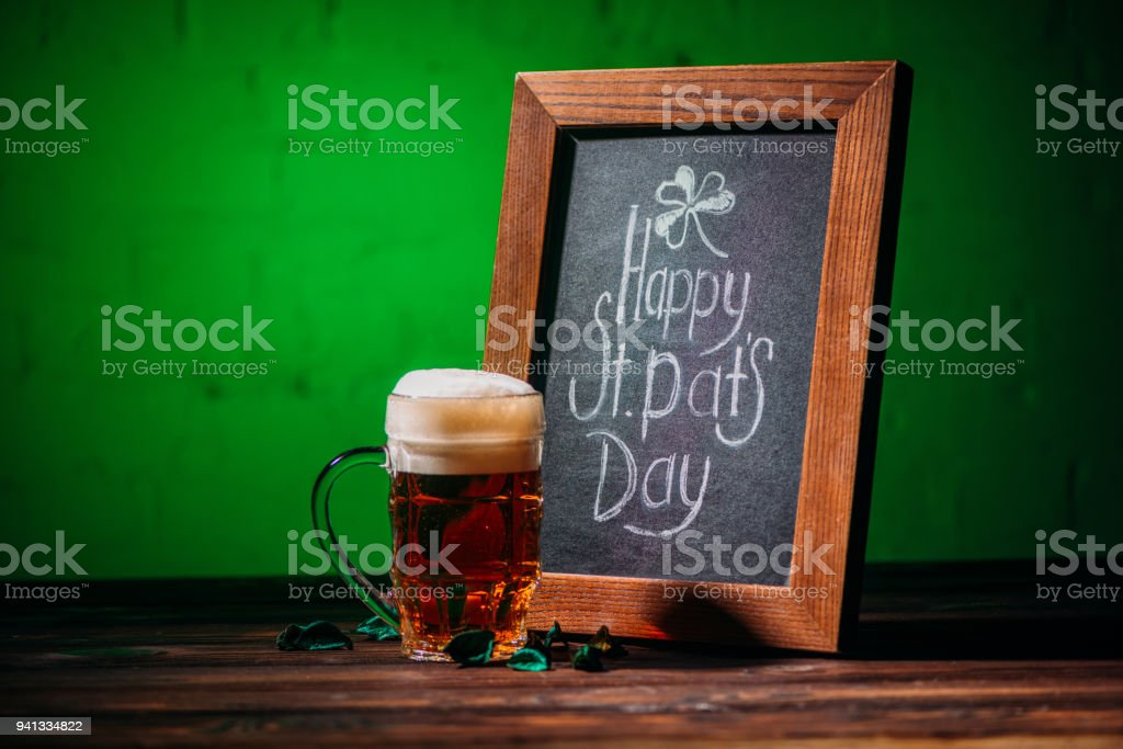 wooden frame with happy st patricks day inscription and glass of beer on table – zdjęcie