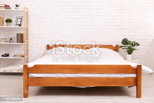 Bedroom interior. Empty wooden framed double bed with two pillows and white blanket, free space. Real photo.
