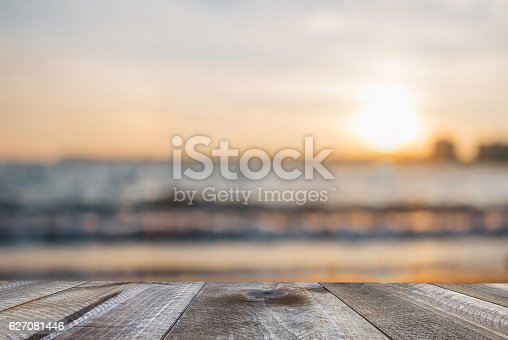 istock Wooden free space on table and sunset over the sea 627081446