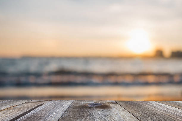 wooden free space on table and sunset over the sea - focus on background stock photos and pictures