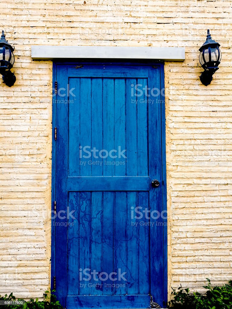 Wooden front door of  blue color and stone wall stock photo