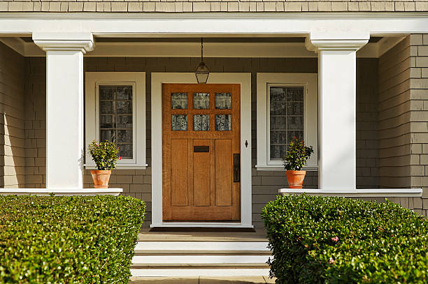 Wooden Front Door A concrete walkway bordered with hedged shrubs leads to the front door of a home. There are windows on either side of the door. Horizontal shot. front door stock pictures, royalty-free photos & images