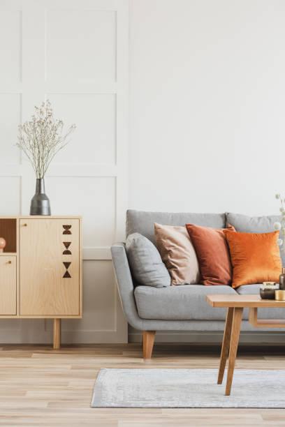 Holzmöbel und graues skandinavisches Sofa mit Kissen im schönen Wohnzimmer-Interieur – Foto