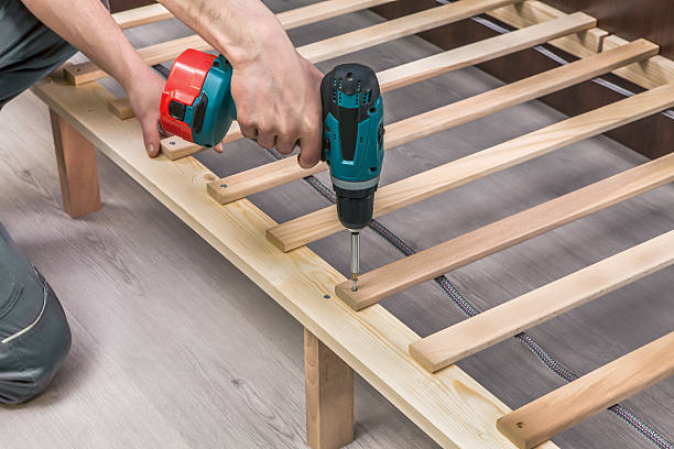 Wooden furniture assembling- woodworker screwing screws using a cordless Wooden furniture assembling- woodworker screwing screws using a cordless cordless phone stock pictures, royalty-free photos & images