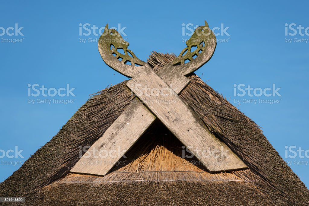 Wooden gabled boards in the form of horse heads on a thatched roof against a blue sky, typical of traditional houses in northern Germany stock photo