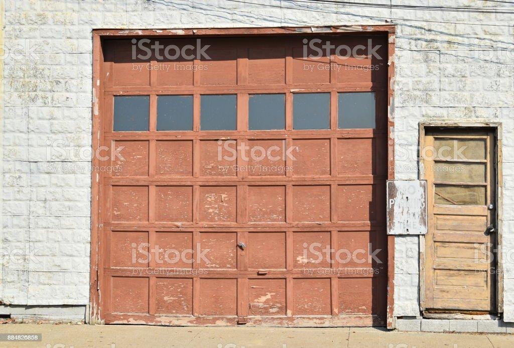 Old wooden garage door with smaller entrance door