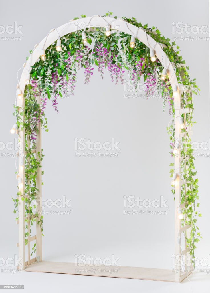 Wooden Garden Arch White Color Decorated With Flowers And Greenery stock photo