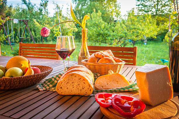 Wooden garden table with bread, cheese and wine Cottage Still Life high scale magnification stock pictures, royalty-free photos & images
