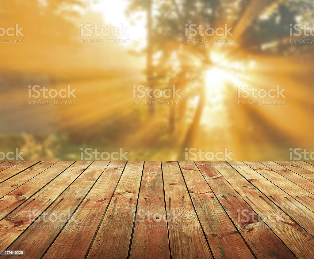 Wooden garden table with sunlight refracting through trees royalty-free stock photo