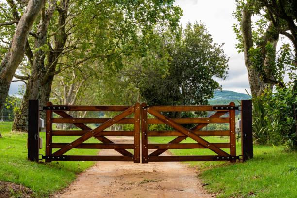 a wooden gate at the entrance to a farm. - portão imagens e fotografias de stock