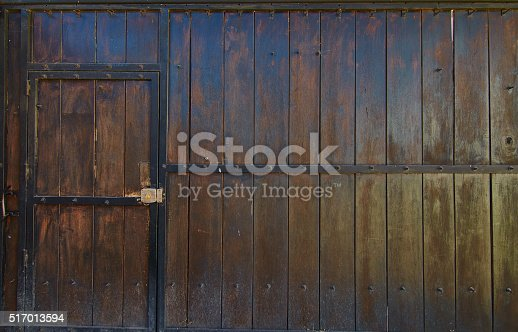 Old wooden gate with a walk through door.  Iron frames the old wood.