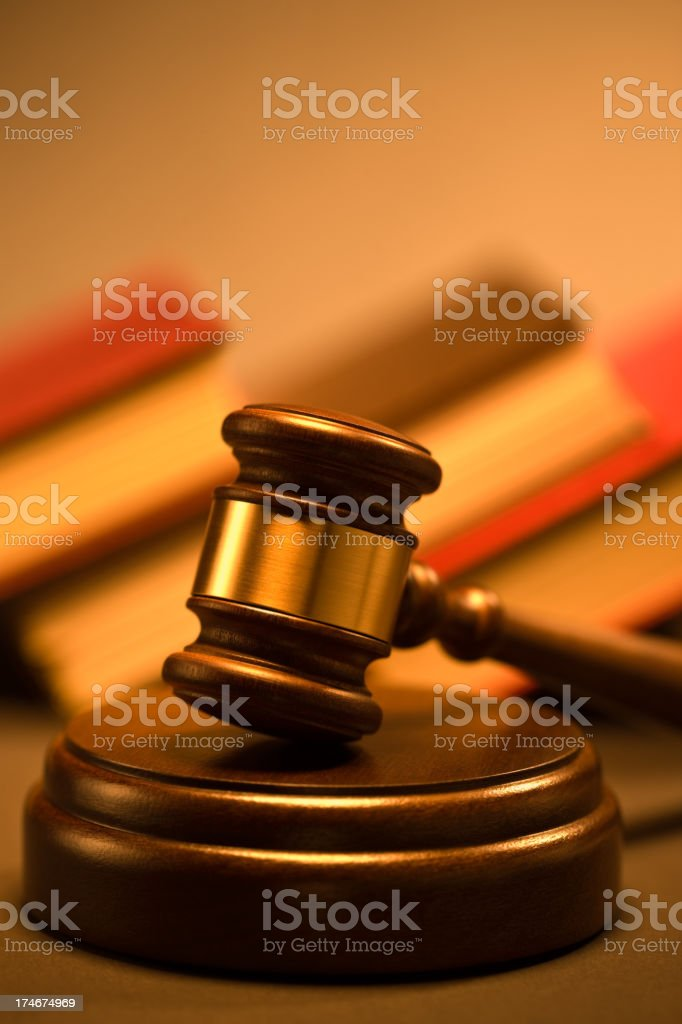 Wooden gavel and law books at the background royalty-free stock photo