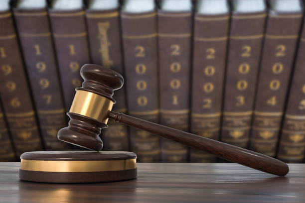 Wooden gavel and law books in lawyers office stock photo