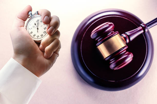 Wooden gavel and stopwatch in male hand stock photo