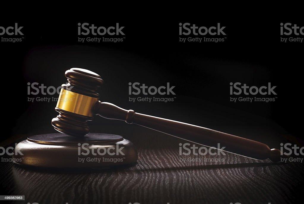 Wooden gavel on a textured dark wood surface stock photo
