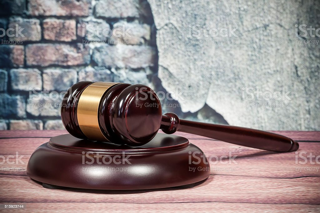 Wooden gavel on a vintage wall background stock photo