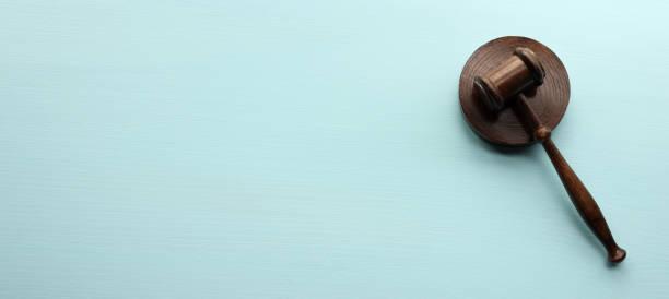 Wooden gavel on blue background stock photo