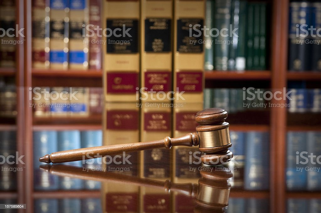 Wooden gavel on reflective table in front of law library stock photo
